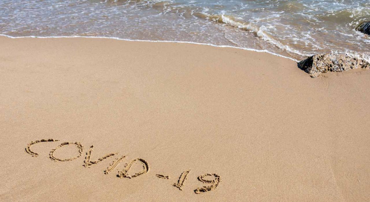 ¿Cómo afectan los ERTE a las vacaciones? Imagen de playa con las palabras covid-19 escrito en la arena