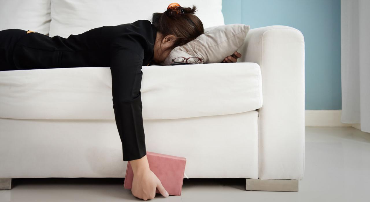 Mujer cansada tumbada en sofá con una libreta en la mano. Absentismo laboral, integridad física y libertad de empresa