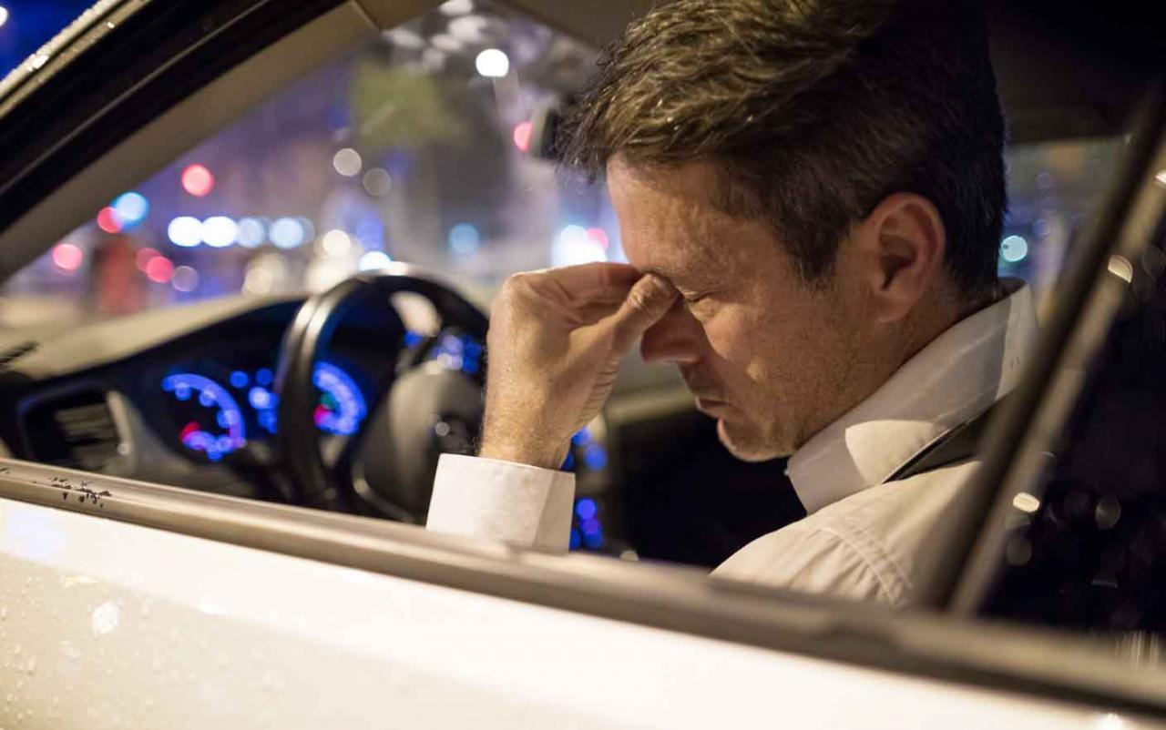 Accidente de trabajo. Imagen de hombre sentado en un coche con gesto de enfermedad