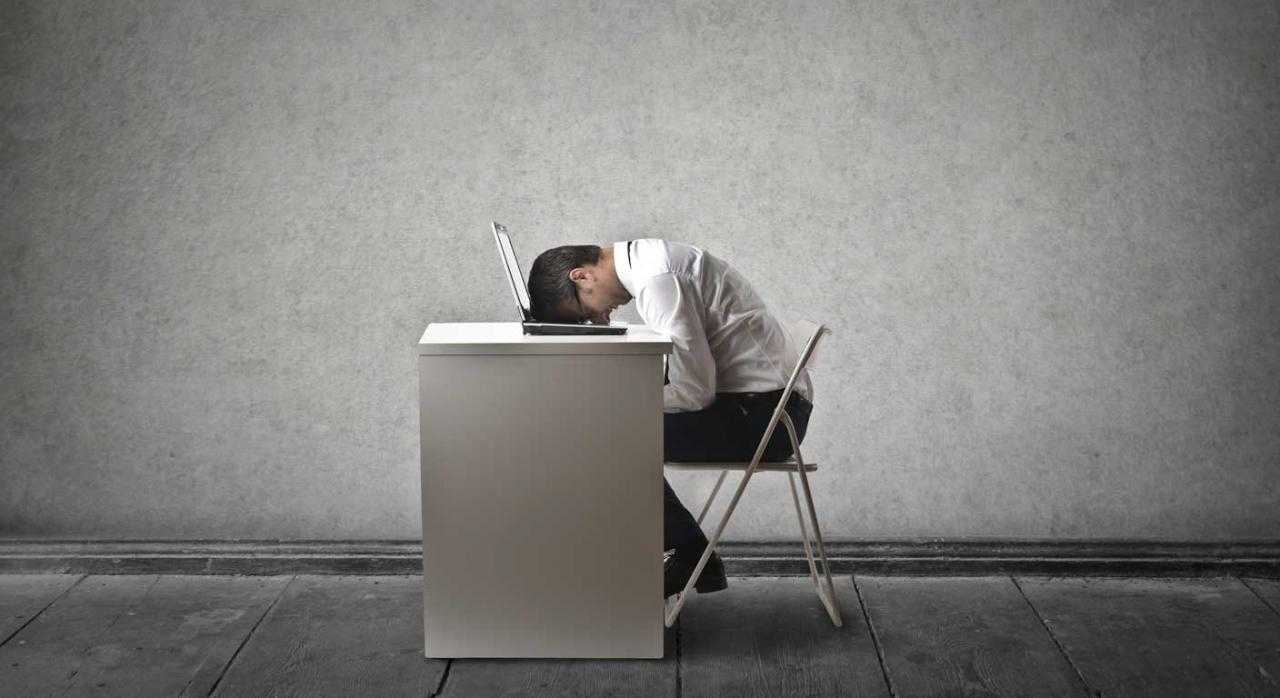 Imagen de un chico dandose un cabezazo con la pantalla del ordenador por el acoso laboral que siente