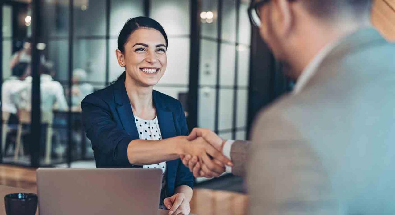 Vacaciones; negociación; representación legal de los trabajadores. Apretón de manos entre una mujer y un hombre en una oficina
