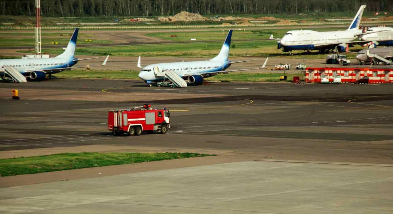 Bomberos de AENA. Camión de bomberos en pista de aeropuerto cerca de varios aviones