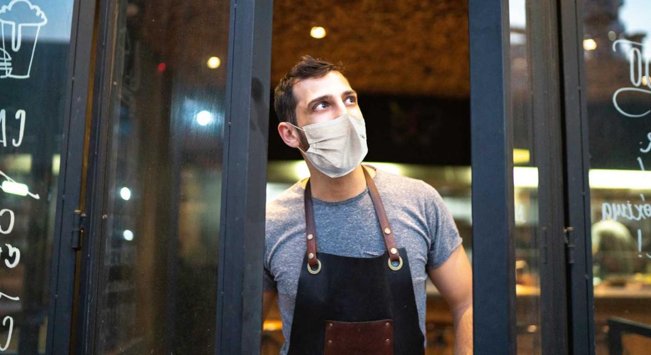 Ayudas para hostelería y autónomos. Empleado con mascarilla cerrando la puerta de una cafetería
