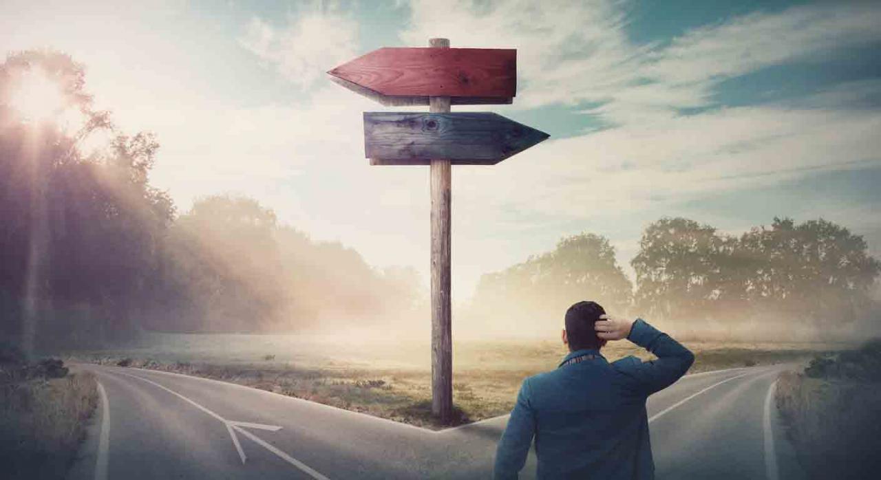 Convenios colectivos; concurrencia; jornada; ultraactividad. Imagen de un hombre dudando en una bifurcación donde hay un poste indicando dos direcciones