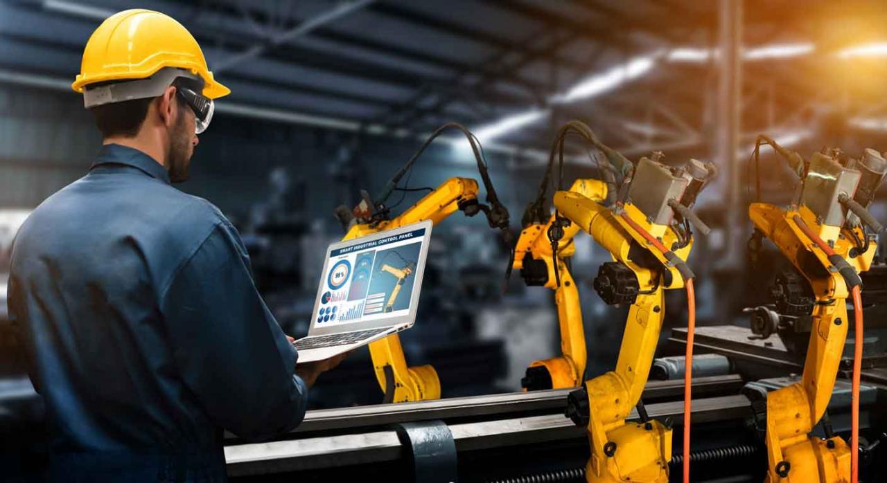 Huelga; esquirolaje interno. Brazos robóticos en una fábrica con tecnología digital, dirigidos por un operario desde un portátil
