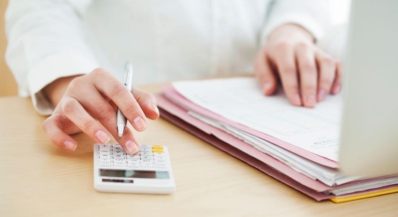 Cálculo del salario. Persona con papeles encima de una mesa y utilizando una calculadora