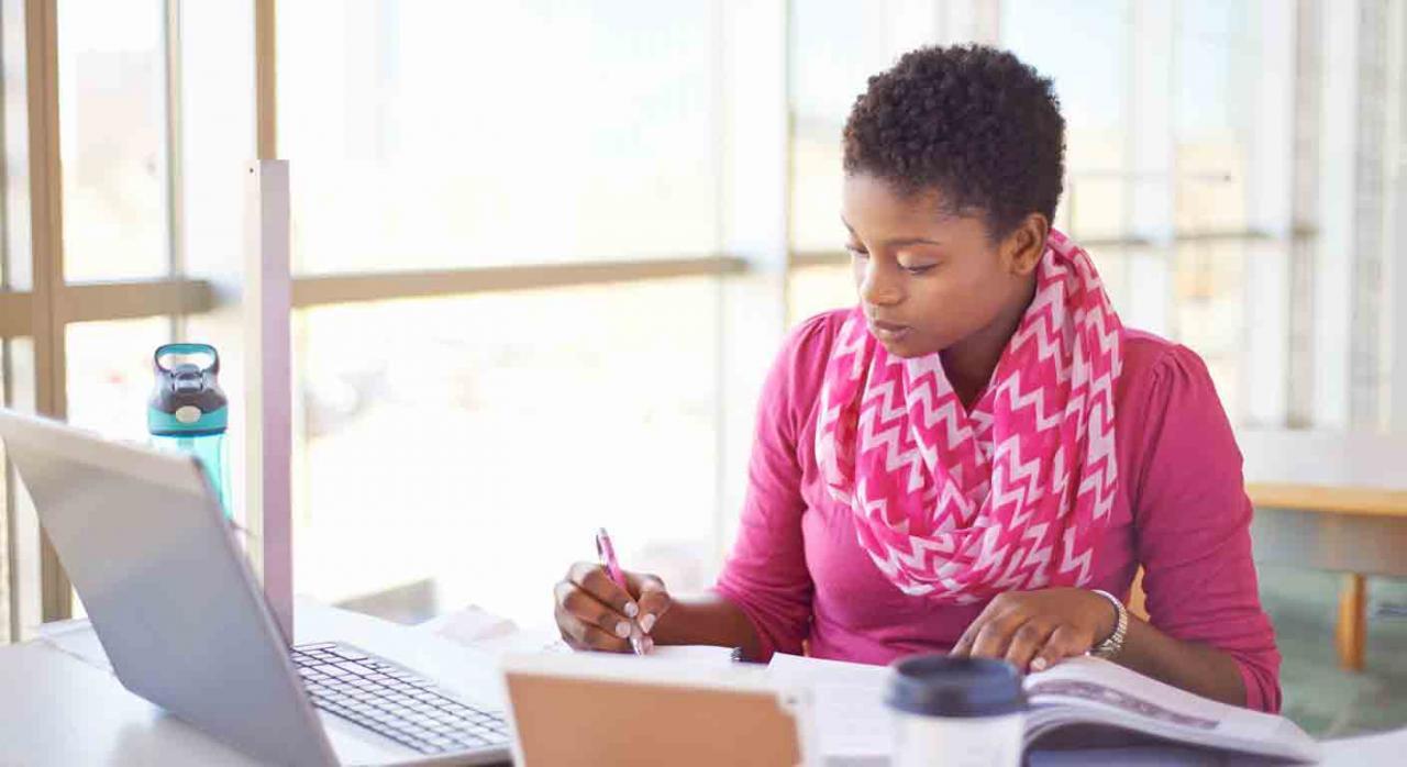 Personal Investigador Predoctoral en Formación. Chica estudiando concentrada en una biblioteca con un ordenador tomando apuntes