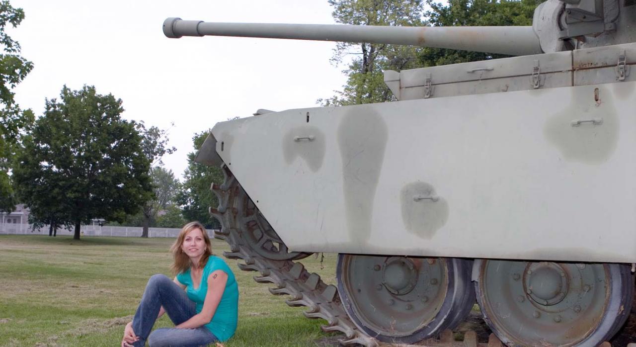 Mujer sentada al lado de un tanque militar