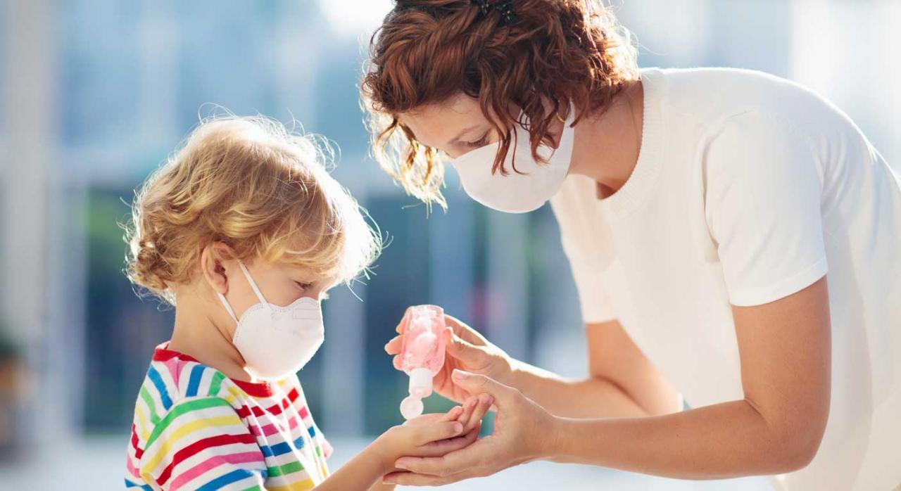 Concursos para la provisión de puestos de trabajo. Madre e hijo con mascarilla desinfectándose las manos