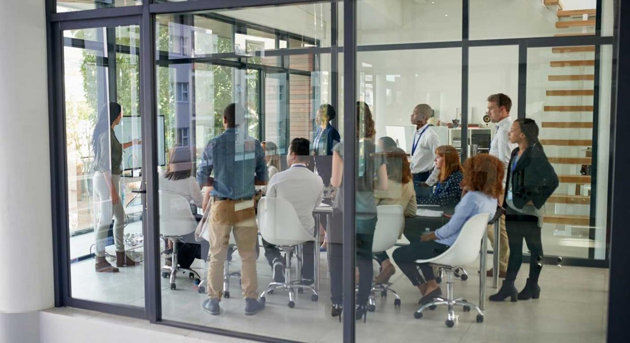Condiciones de trabajo. Grupo de trabajadores dentro de un despacho acristalado