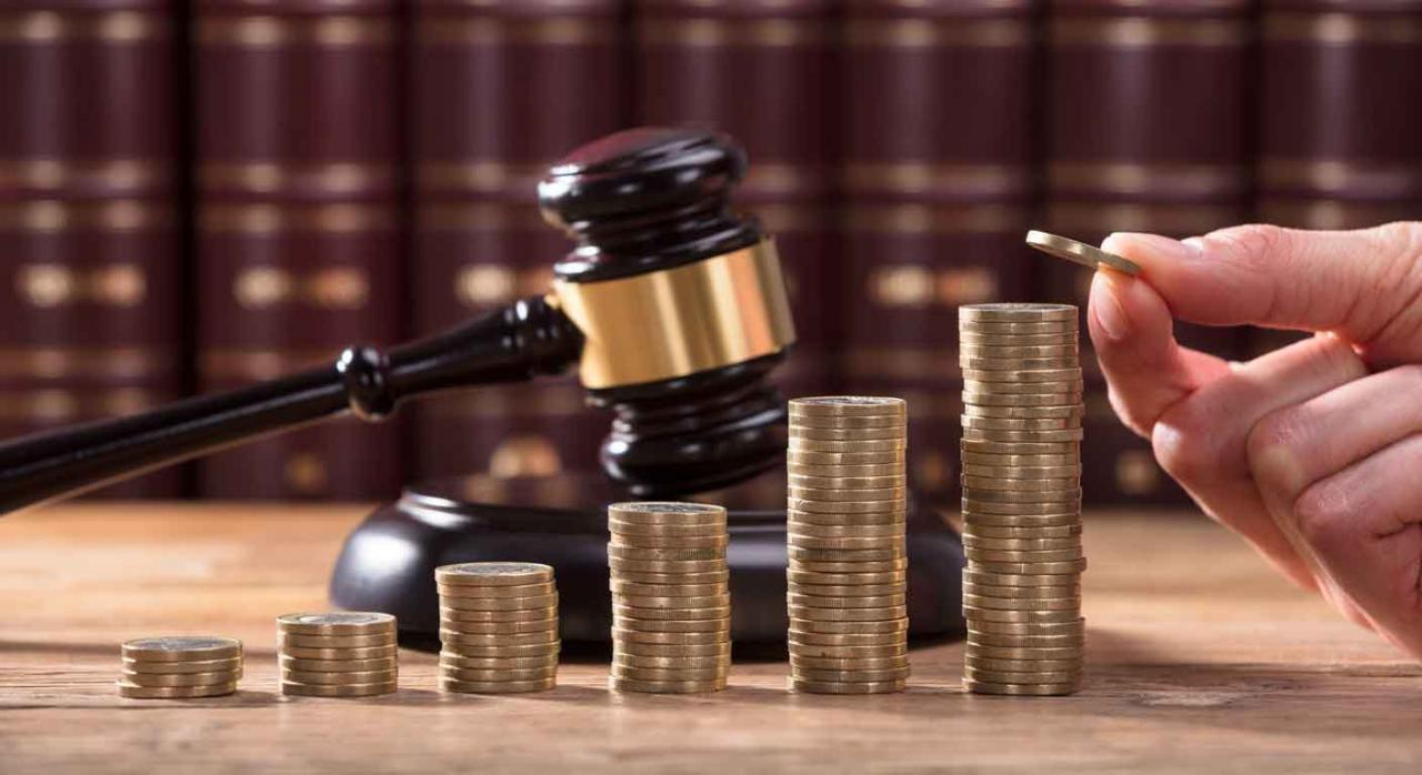 Imagen de unas monedas en escala con una maza de juez para solucionar conflictos colectivos