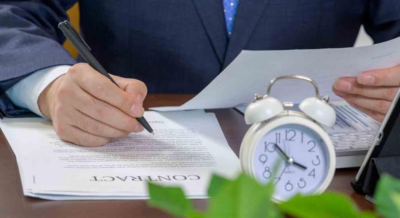 Empresario revisando un contrato y reloj sobre la mesa