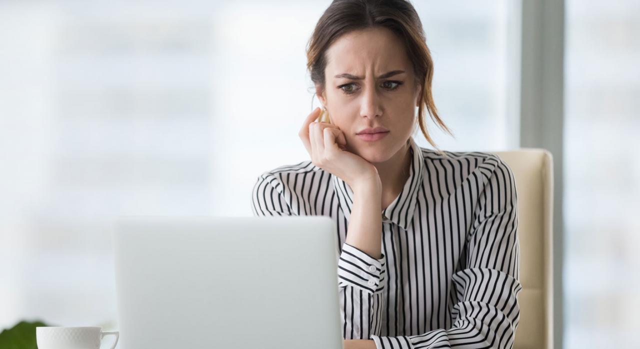 Trabajadores con contrato indefinido a tiempo parcial que realizan su actividad de manera compactada. Imagen de una mujero mirando la pantalla del ordenador con cara preocupante