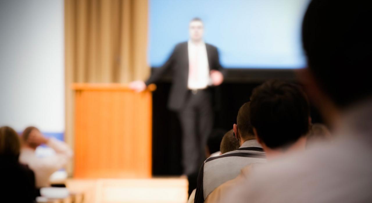 Contratos predoctorales. Imagen difuminada de un hombre dando una conferencia