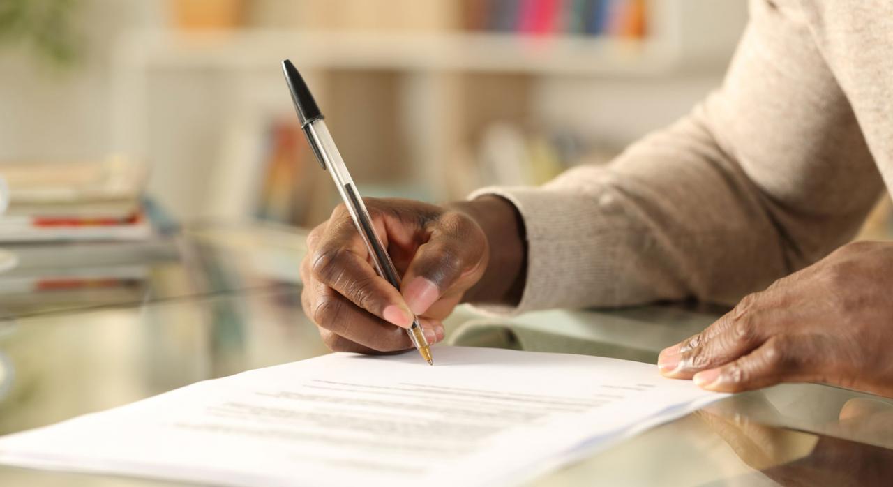 El pacto novatorio puede tener una limitación temporal. Imagen de las manos de un hombre negro firmando un papel sobre una mesa