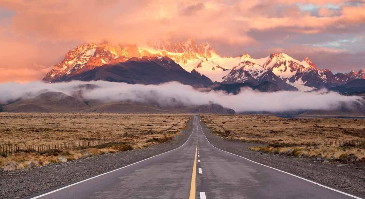 Convenios Colectivos. Vista de una carretera vacía con montañas de fondo y cielo anaranjado