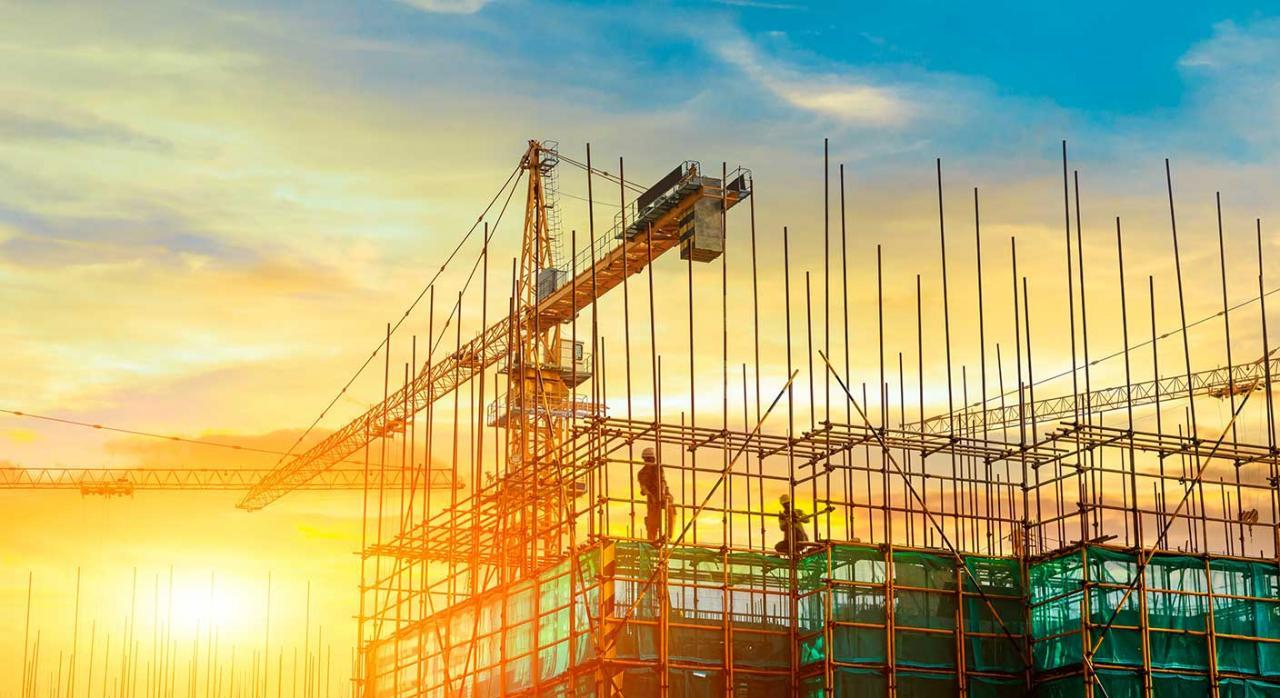 Convenios Colectivos. Imagen de la grúa de una torre y la silueta de un edificio en construcción