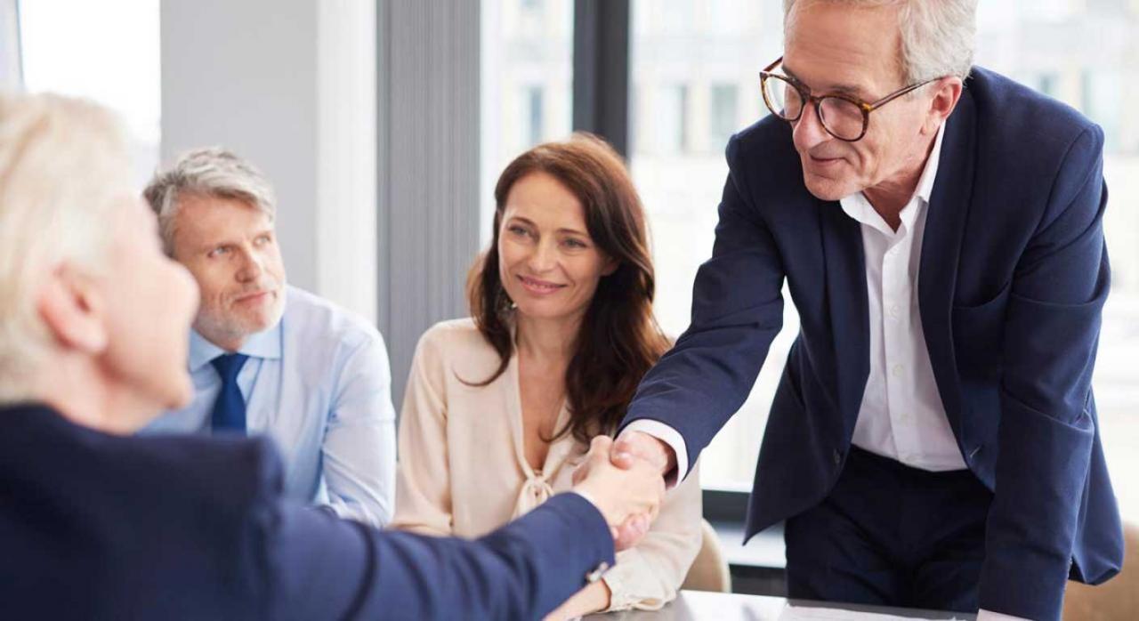 Convenios Colectivos. Dos personas dándose la mano en una reunión