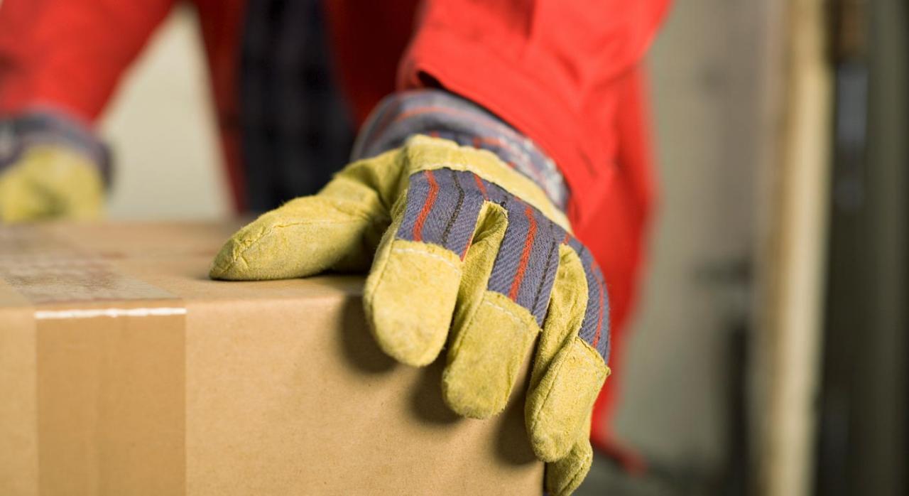 Imagen de caja de cartón sujetada por una persona con guantes