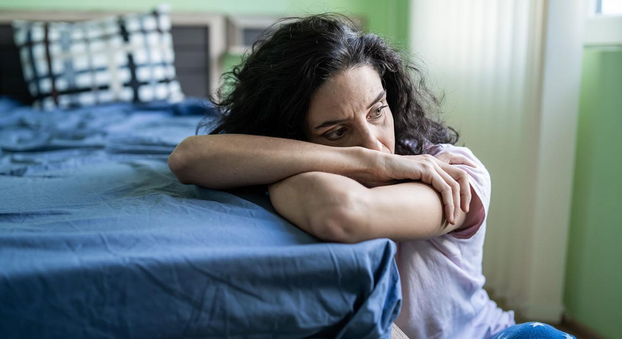 COVID-19; violencia de género; estado de alarma. Imagen de una mujer preocupada sentada al lado de cama