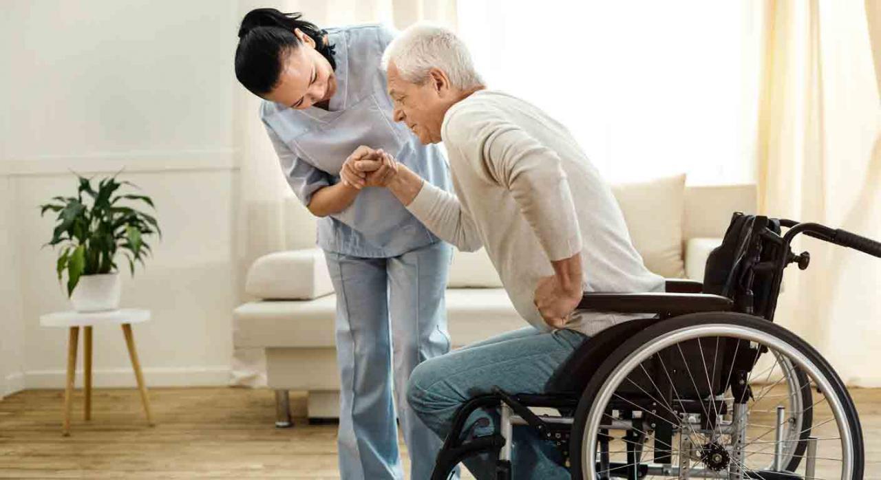 Gran invalidez. Sanitaria ayudando a un hombre mayor a levantarse de la silla de ruedas