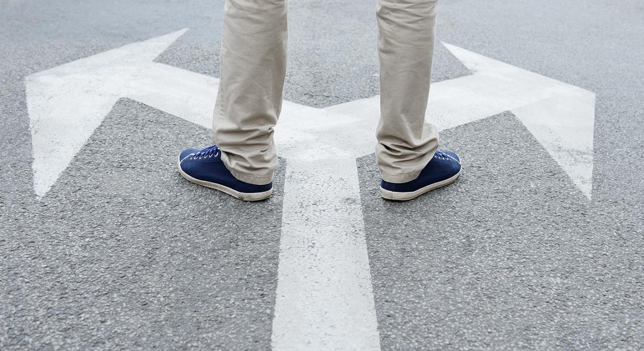 Desempleo; derecho de opción. Imagen de un hombre pisando unas flechas en el suelo