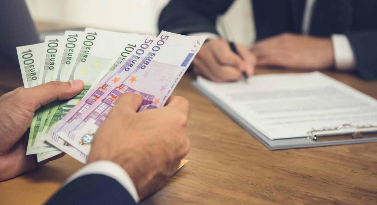 Empresario contando billetes de euro mientras tramitan un acuerdo