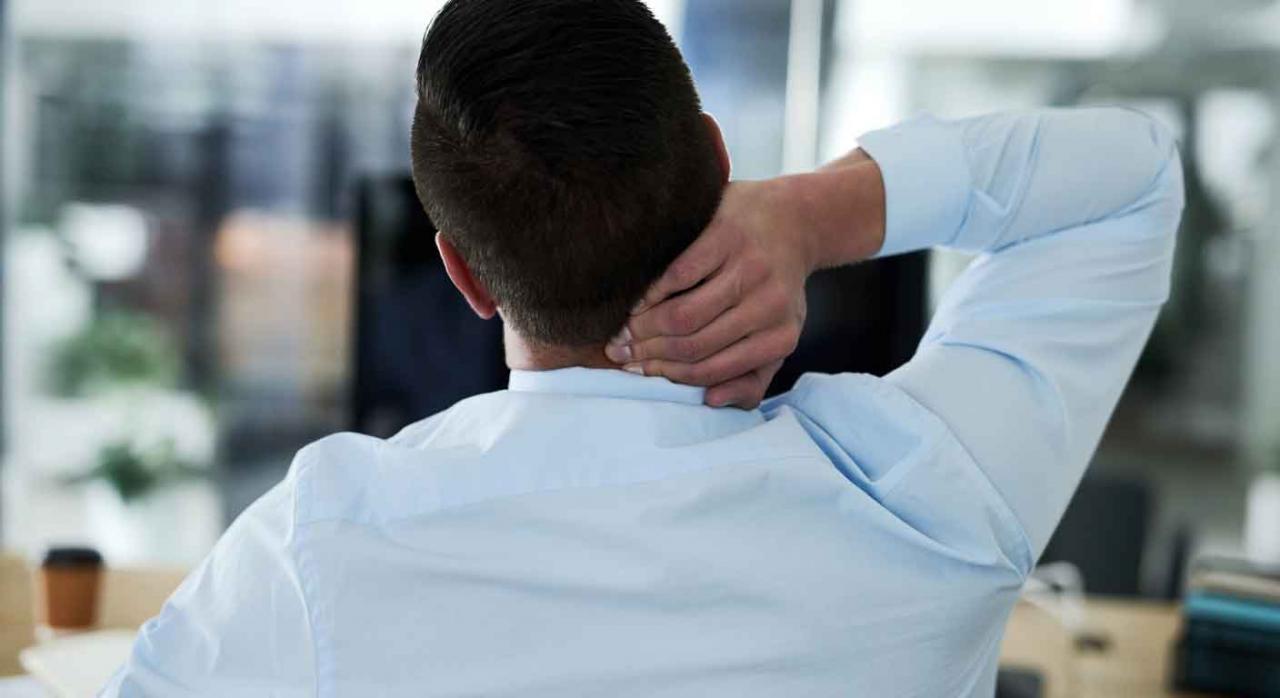 Hombre sentado en su oficina con dolor de cuello