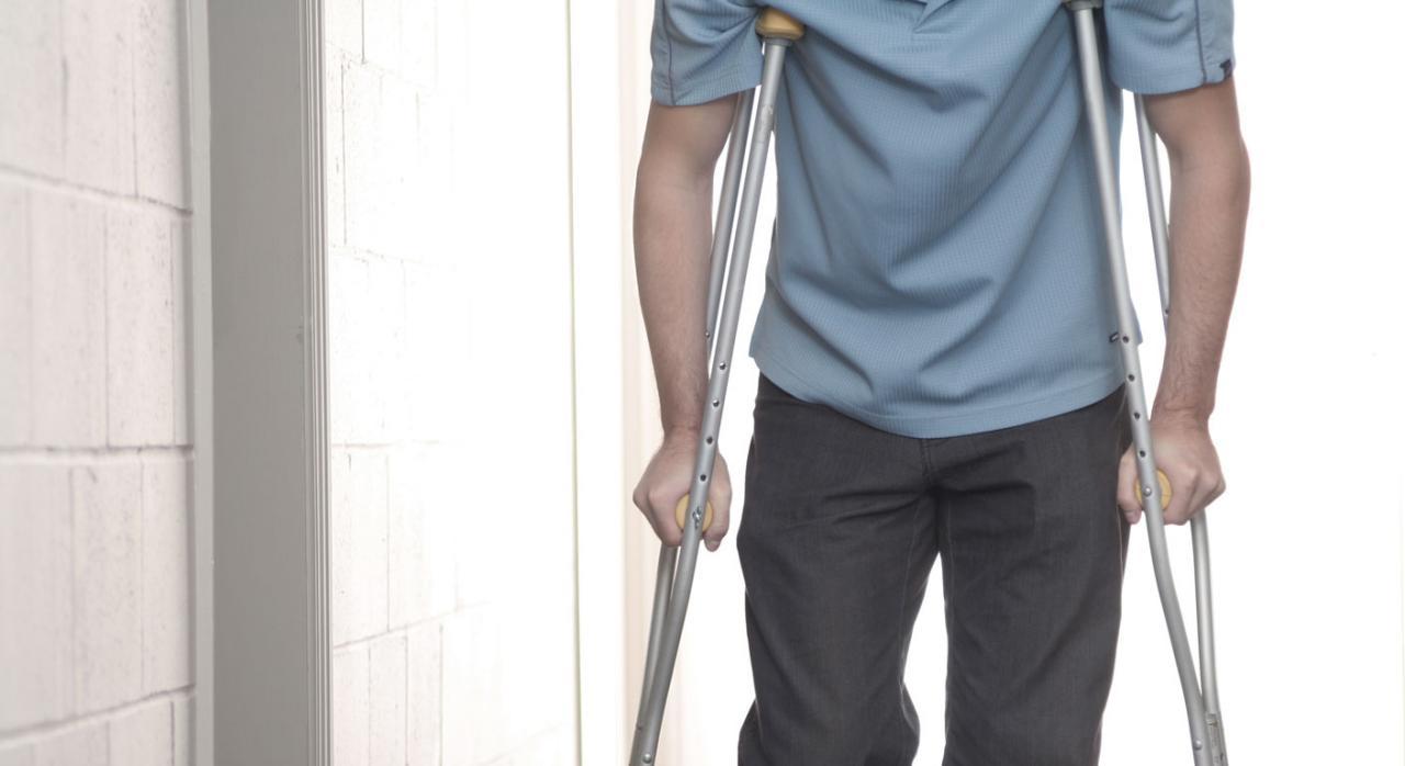 Personas con minusvalía o personas con discapacidad. Jóven caminando con muletas