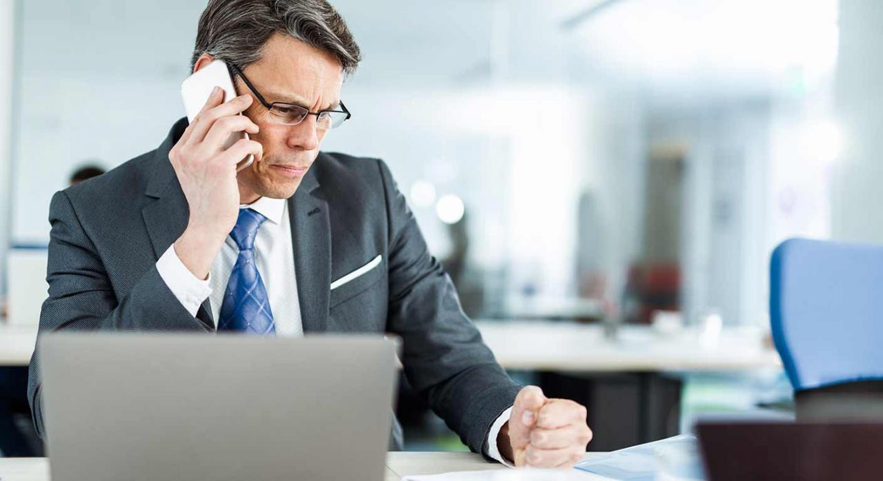 Ejecución de sentencias de despido; readmisión. Imagen de un hombre de negocios enojado hablando por teléfono