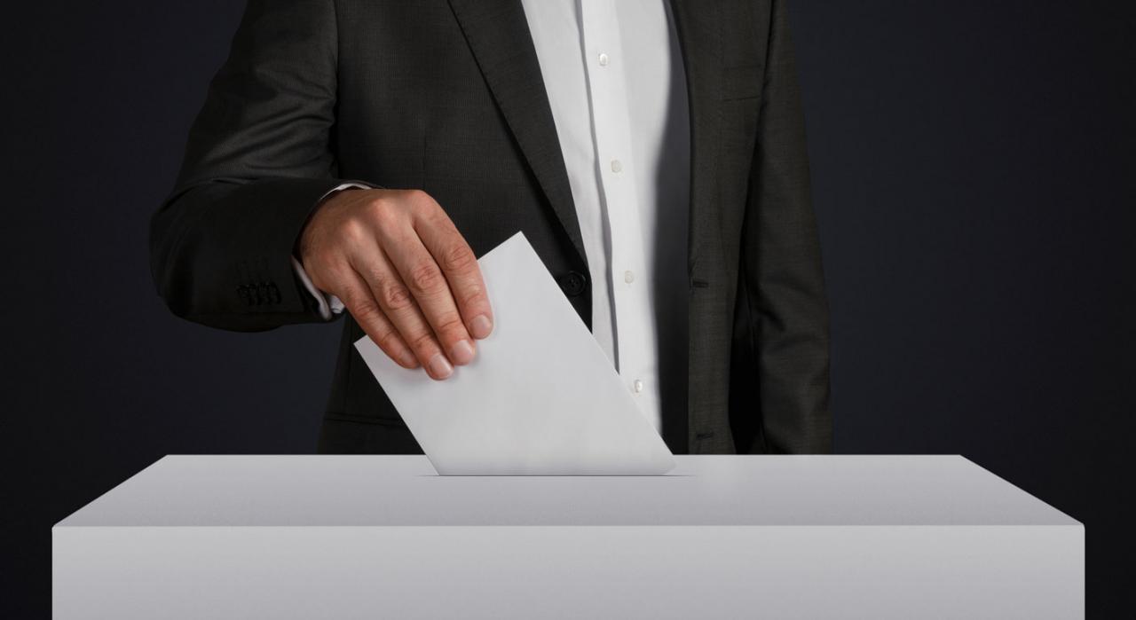 El centro de trabajo constituye la unidad electoral básica. Imagen de hombre metiendo papeleta en una hurna
