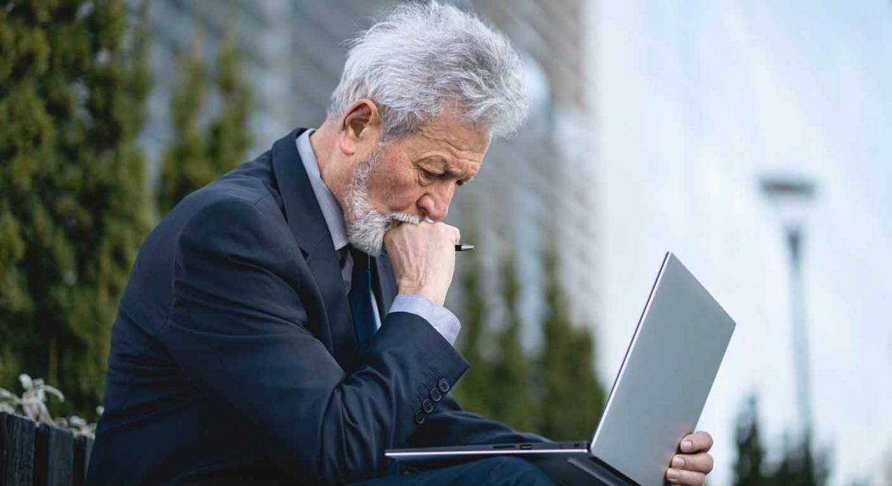 Jubilación parcial; jornada concentrada; suspensión colectiva; desempleo. Ejecutivo mayor sentado en un banco en la calle mirando preocupado el portátil