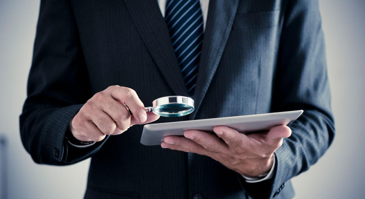 Empresario sostiene lupa y tableta digital para comprobar el registro de jornada