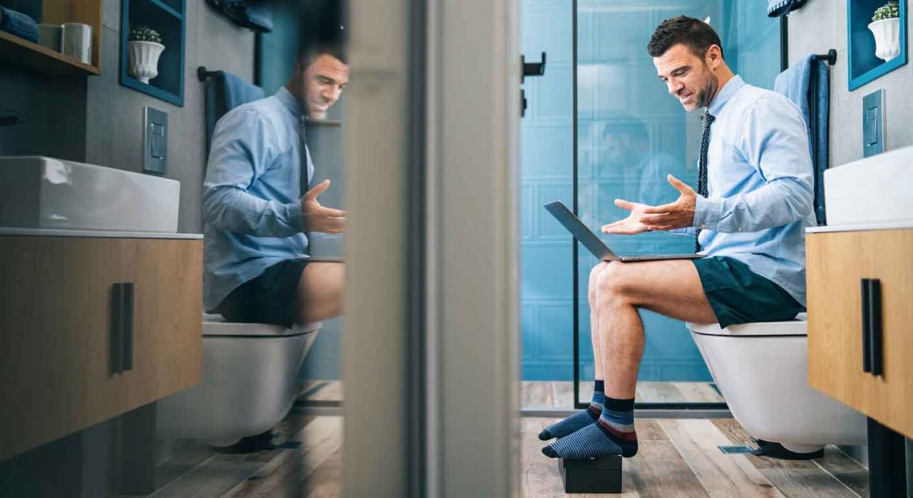 Contact center; uso del lavabo; registro de jornada. Empresario con el portátil sobre las rodillas trabajando en el baño de su casa