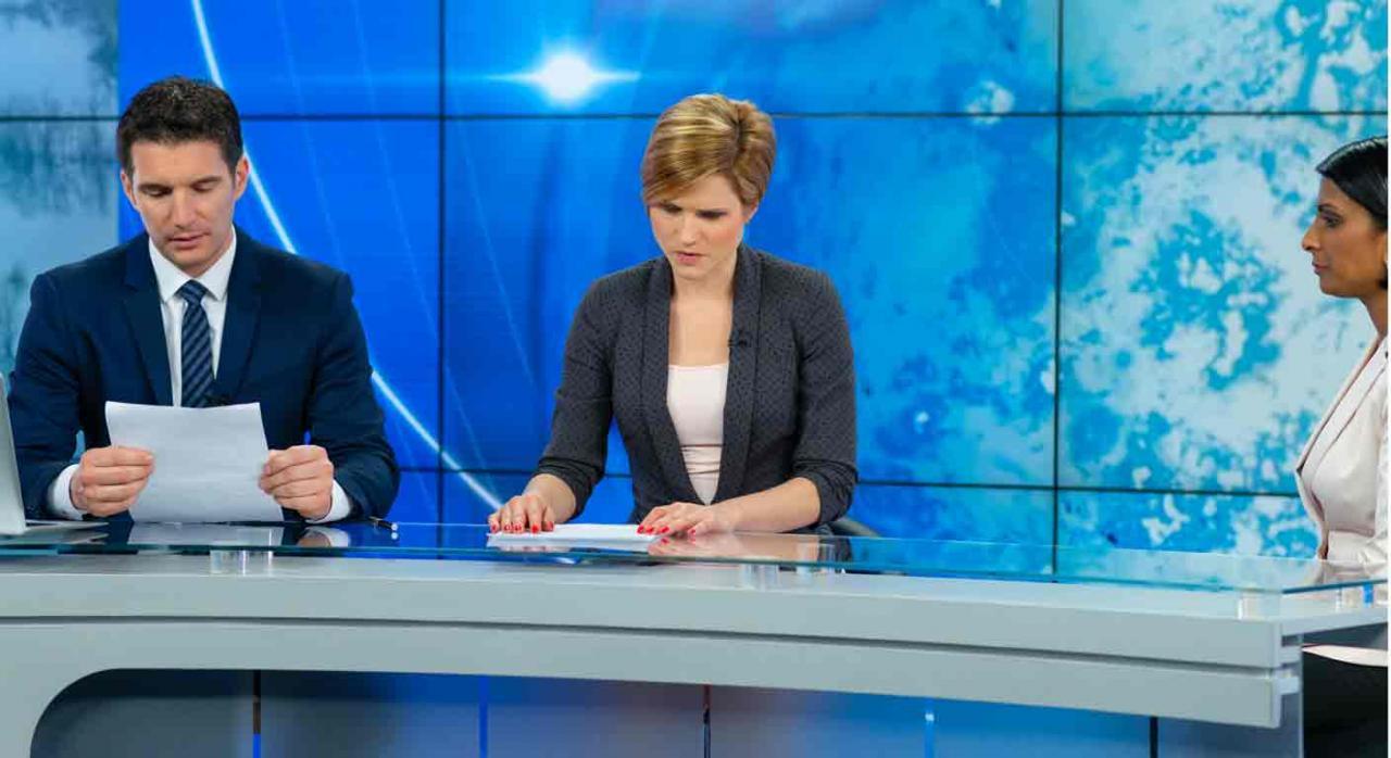 Interinidad por sustitución. Dos presentadores de noticias de TV, comprobando sus notas antes de empezar