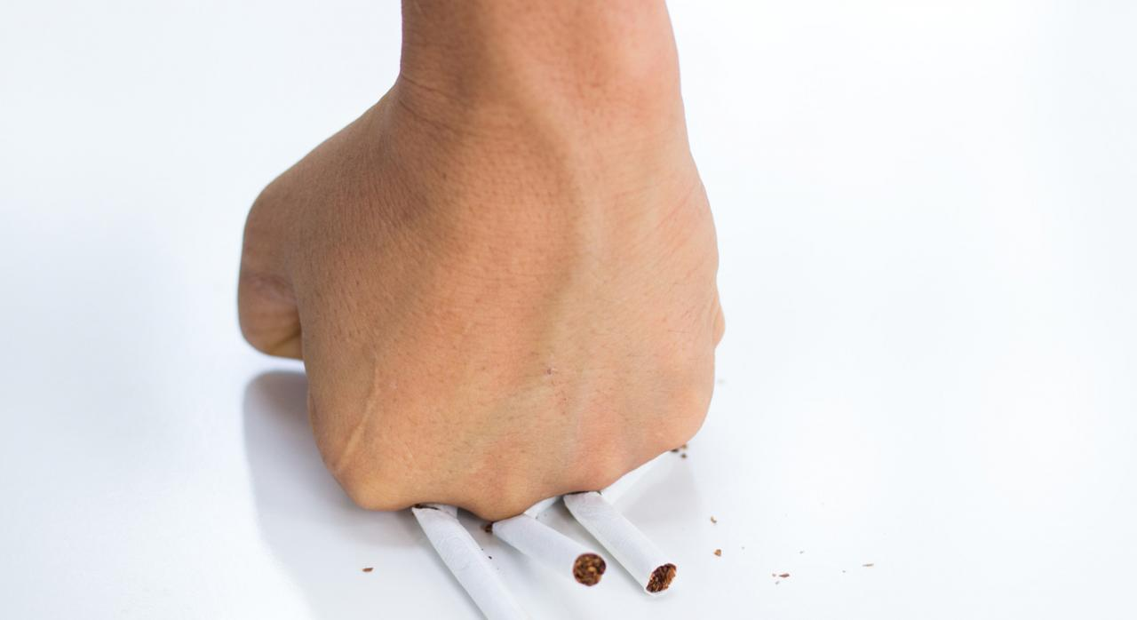 Mano aplastando cigarrillos