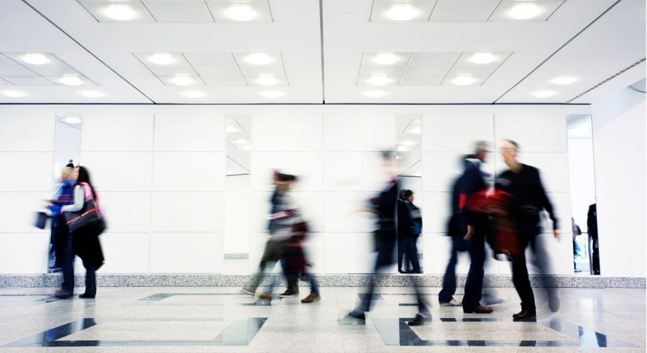 Imagen de un grupo de gente caminando por un pasillo iluminado. Pliego cláusulas administrativas