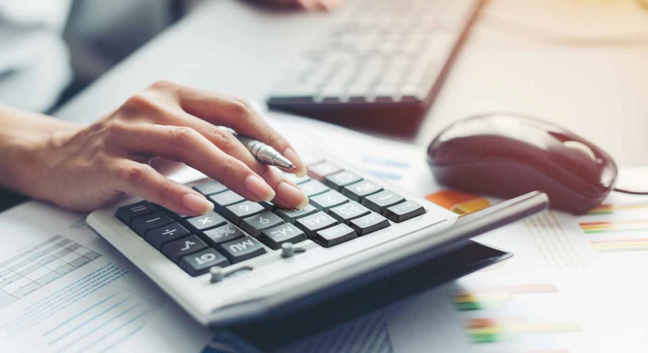 Gran invalidez. Mujer frente a un teclado, haciendo cálculos con una calculadora