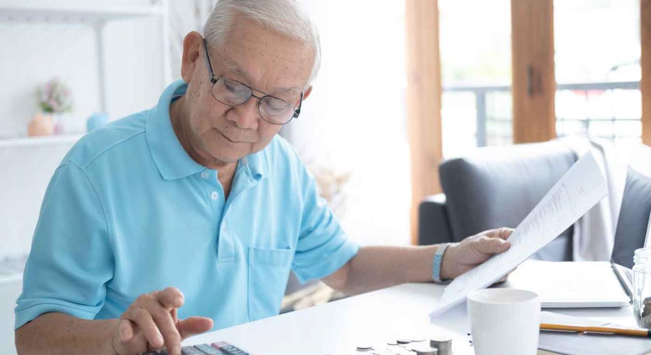 Jubilación; RETA; imputación de pagos. Hombre mayor en casa, usando calculadora, con unas monedas sobre la mesa y unas hojas en la mano