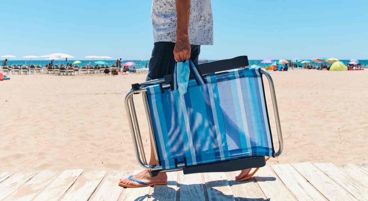 Vacaciones ERTE. Hombre entrando en la playa con una silla plegable