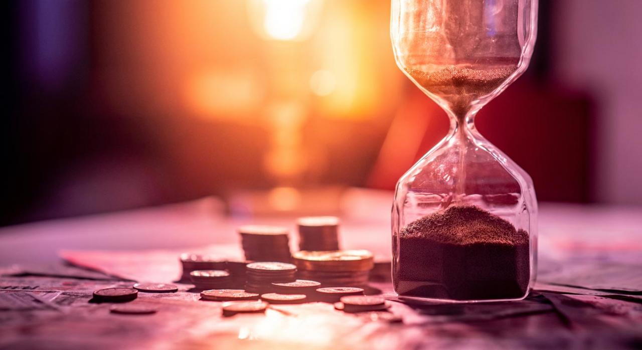 La pensión de IPT es incompatible con la profesión habitual. Imagen de reloj de arena sobre mesa con billetes y monedas