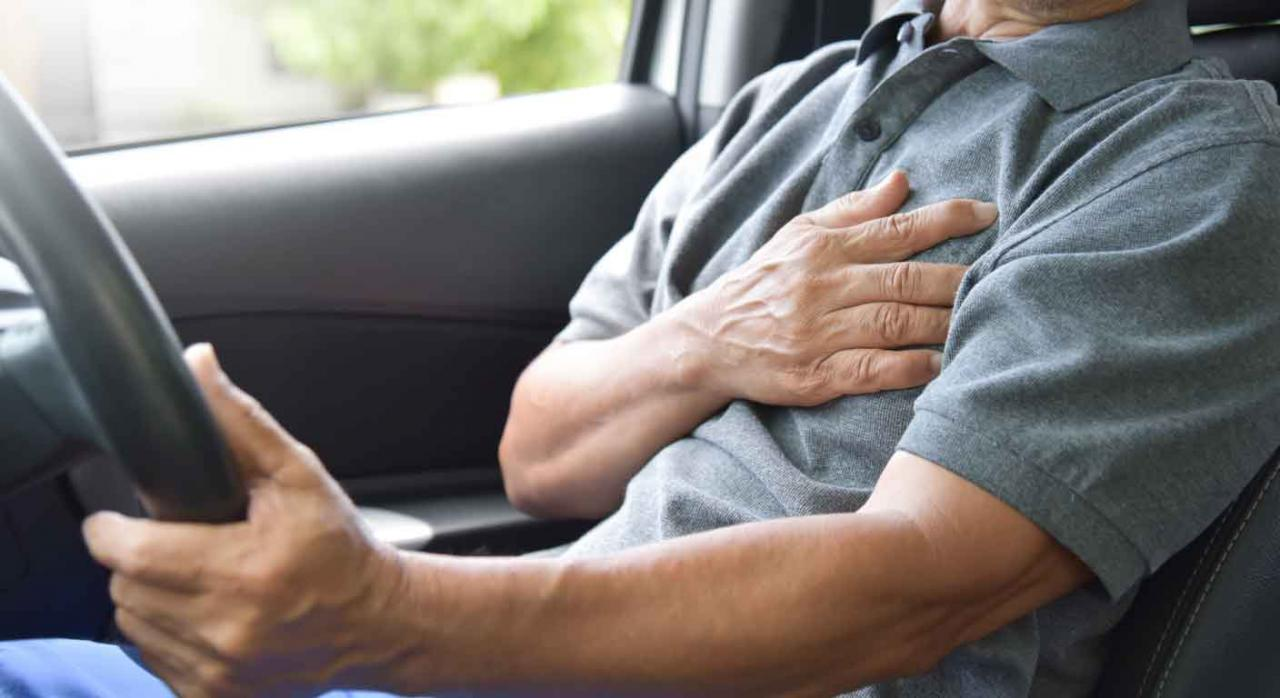 Infarto de miocardio. Imagen de un señor conduciendo con la mano en el corazón