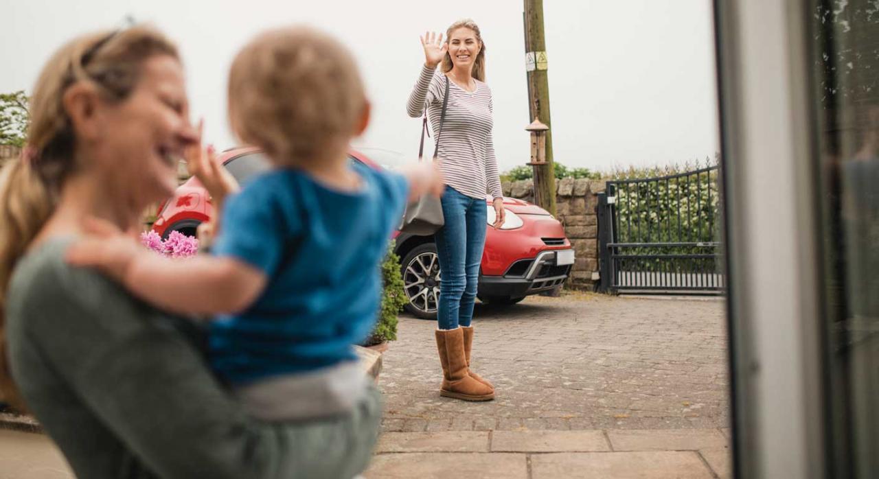 Imagen de una mama despidiendose de su bebe que lo deja con la abuela mientras iba en viaje in itinere al trabajo