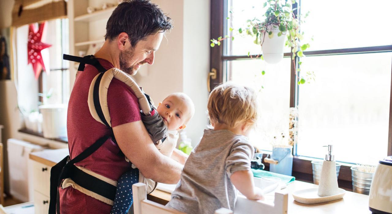 Padre y dos niños pequeños que lava los platos. Jornada de adaptación de reducción de turnos parental