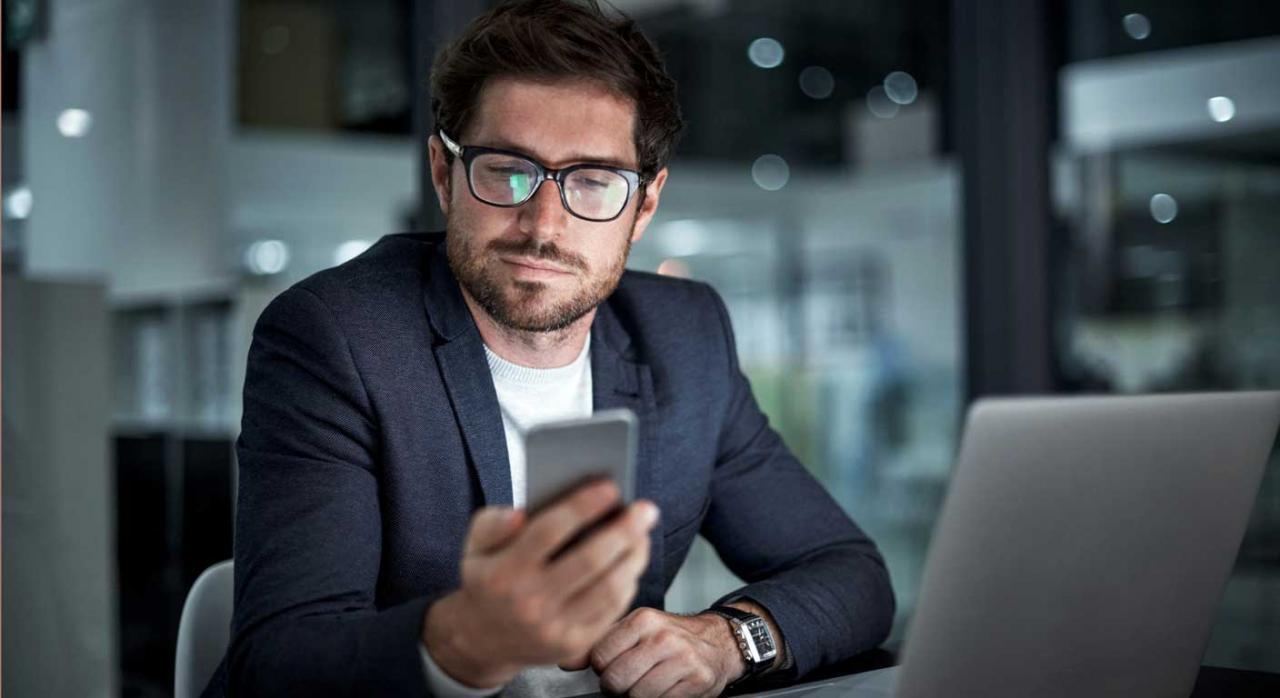 Jubilación parcial y contrato de relevo. Hombre sentado frente a una mesa con portátil, mirando la pantalla de un móvil