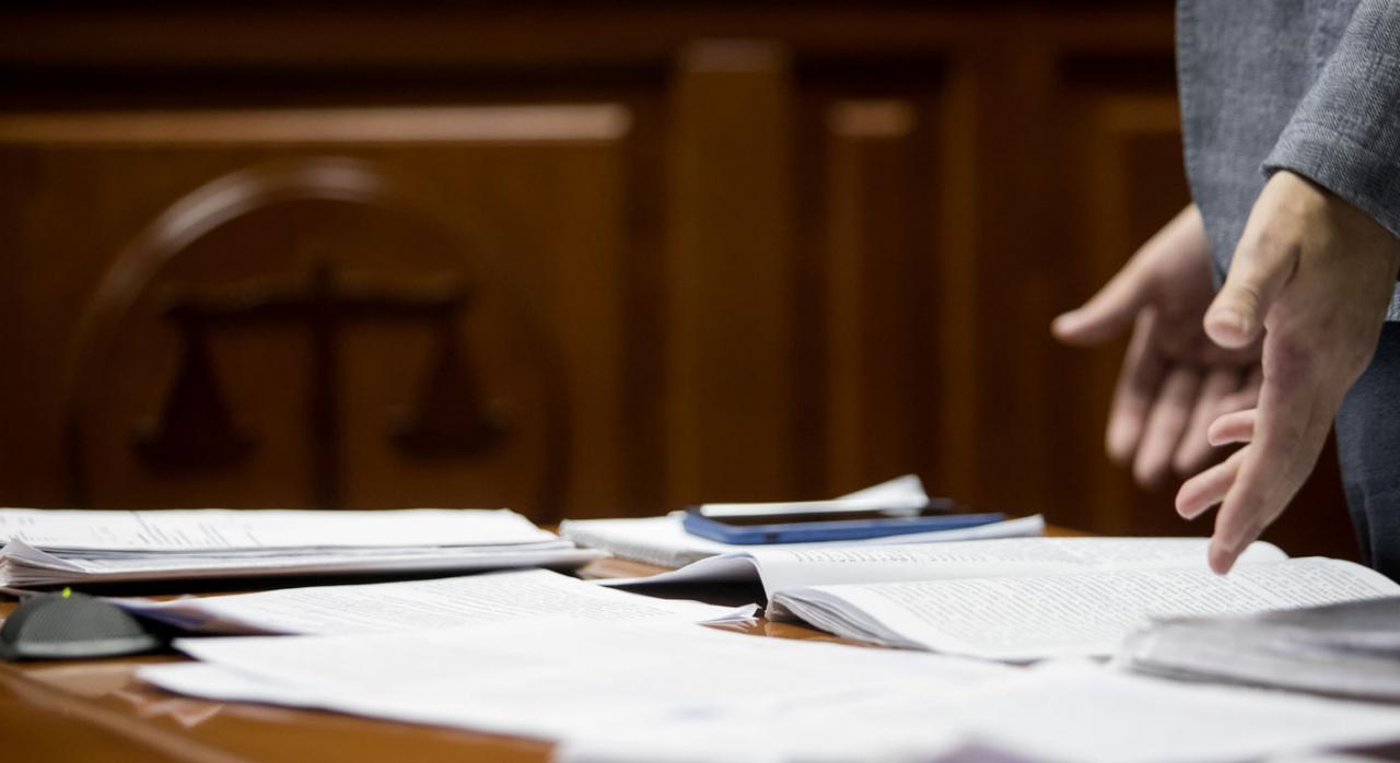 Legitimación de la empresa demandada para recurrir en casación unificadora. Imagen de mesa con papeles y dos manos señalándolos
