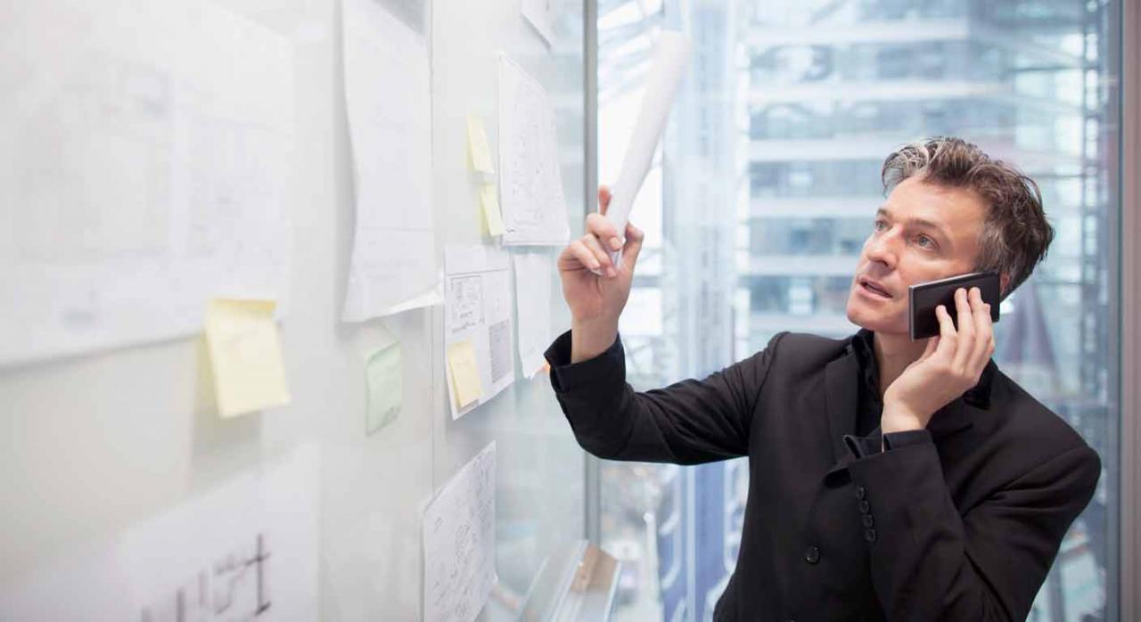 Hombre mira unas listas mientras habla por teléfono