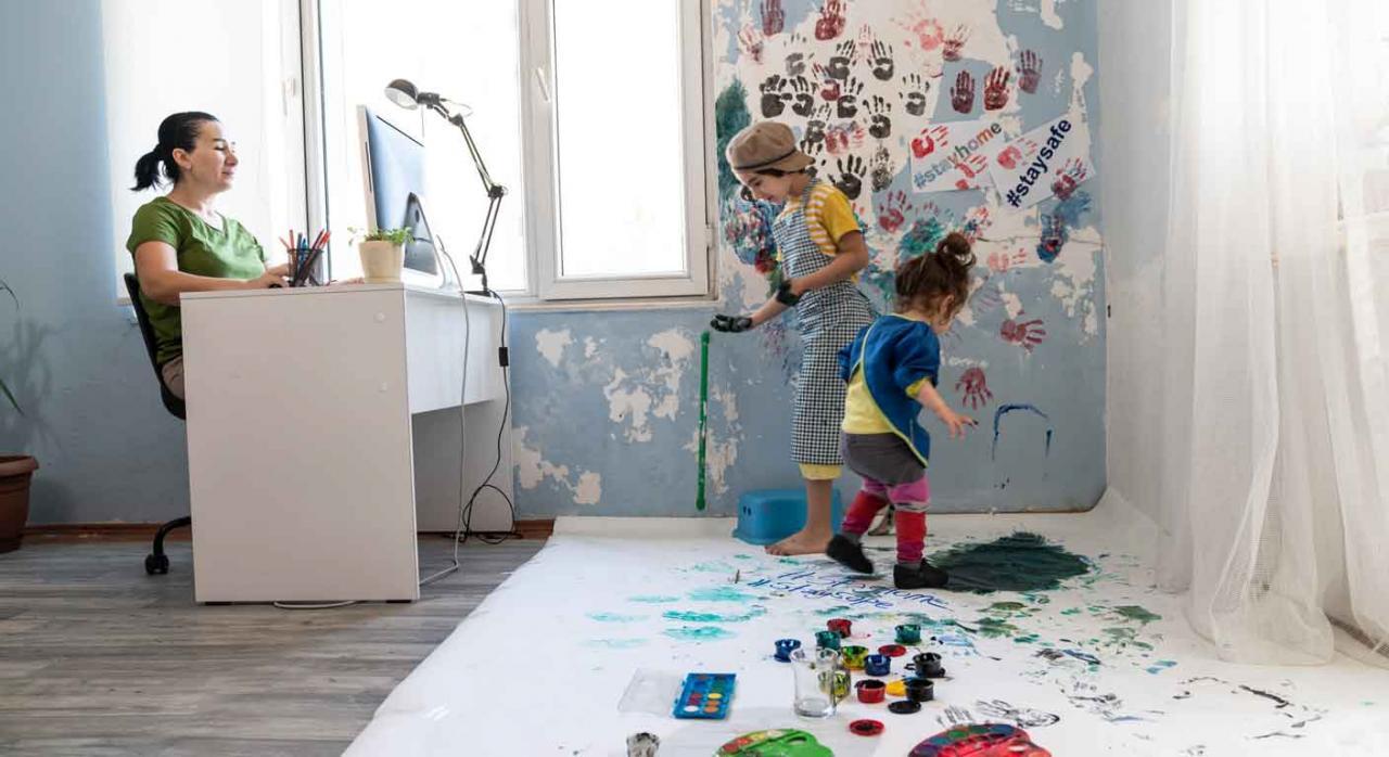 teletrabajo; conciliación; negociación. Madre teletrabajando mientras vigila a sus dos hijos mientras juegan