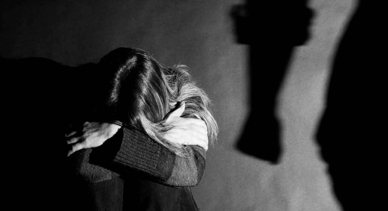 Viudedad; parejas de hecho; violencia de género. Mujer asustada tapándose la cara y la sombra de un hombre con el puño reflejado en la pared