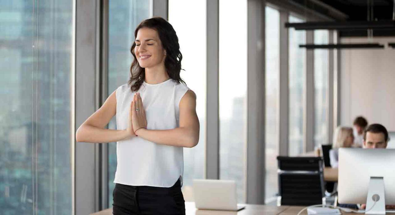 Mindfulness. Mujer sonriente haciendo yoga en la oficina